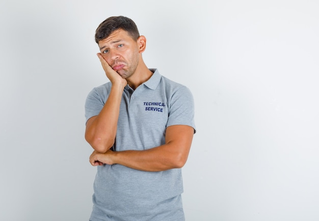 Technische dienst man leunend zijn wang op opgeheven handpalm in grijs t-shirt en boos kijken