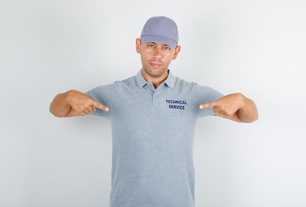 Technische dienst man toont zichzelf in grijs t-shirt met pet en kijkt zelfverzekerd