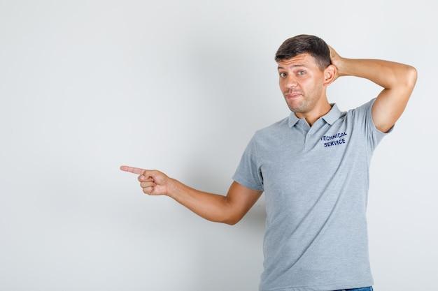Technische dienst man wijst naar kant met hand op hoofd in grijs t-shirt en kijkt verlegen