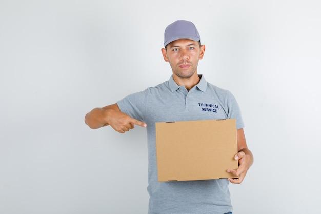 Technische dienst man wijzende vinger op kartonnen doos in grijs t-shirt met pet