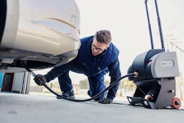 Technische keuring van de auto. autodiagnose op technische keuring, auto-elektronica. een man in een blauw uniform houdt een digitizer vast en controleert de staat van de elektronica onder de auto