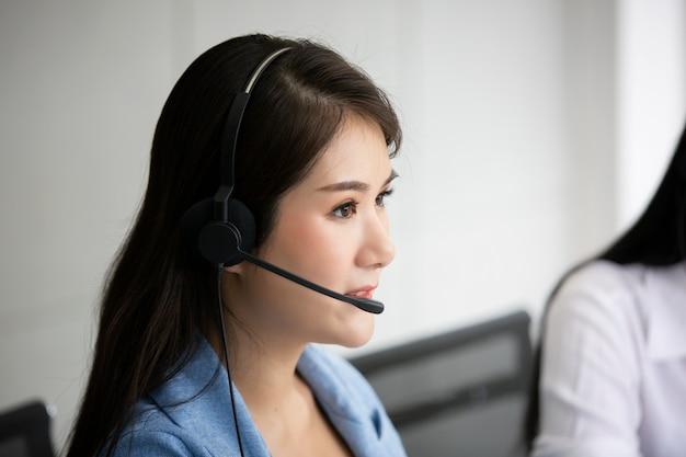 Technische ondersteuning exploitant met hoofdtelefoon werkt op laptop en computer