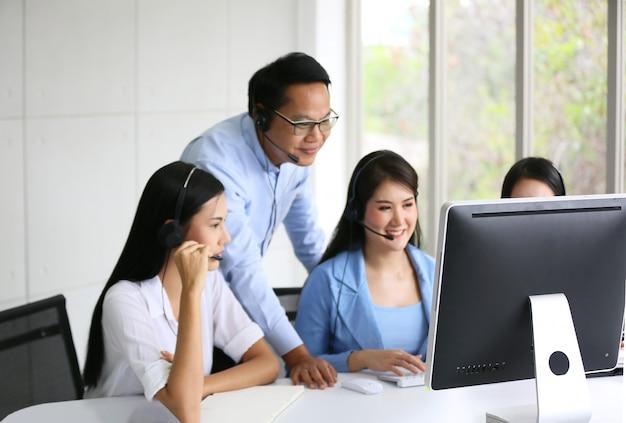 Technische ondersteuningsexploitant met hoofdtelefoon die bij laptop en computer werkt