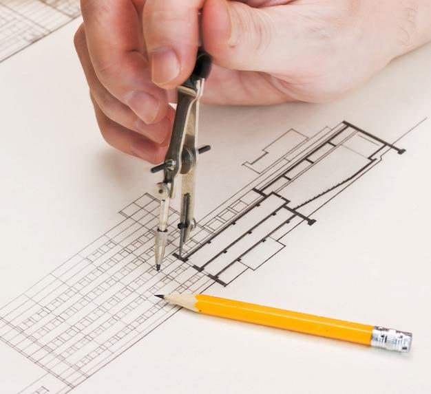 Technische tekeningen en hand met een potlood