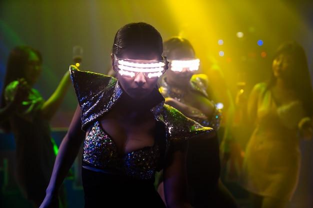 Techno-danseres in nachtclub dansen op het ritme van muziek van dj