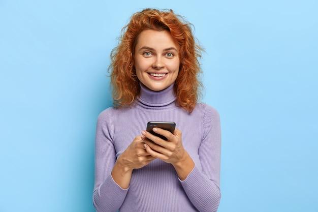 Technologie afhankelijkheid concept. aangenaam uitziende vrolijke vrouwelijke tiener met natuurlijk golvend rood haar