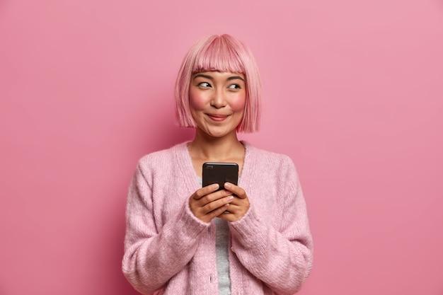 Technologie, communicatie en levensstijlconcept. blij dromerige vrouw met geverfd roze haar, houdt mobiele telefoon vast, gebruikt moderne app om berichten te sturen met vrienden,