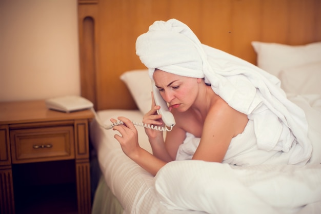 Technologie, communicatie en mensenconcept - de jonge vrouw die in bed liggen en spreekt telefonisch thuis slaapkamer
