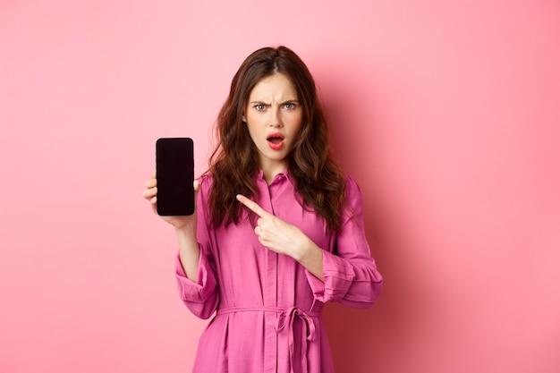 Technologie concept. boos meisje wijst naar haar smartphonescherm en staart veroordelend naar de camera, eist antwoorden of uitleg, staande over de roze muur.