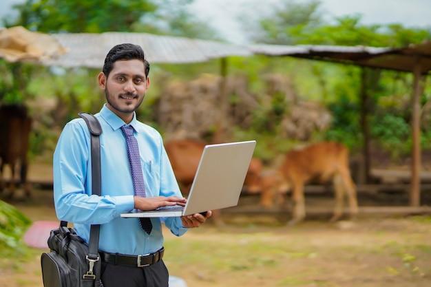 Technologie concept: jonge indiase agronoom of bankier met behulp van laptop.