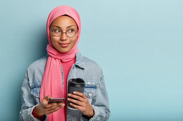 Technologie en communicatieconcept. foto van tevreden moslimvrouw in roze sluier, nieuwe geïnstalleerde smartphoneapplicatie gebruikt, koffie houdt om te gaan, ronde bril draagt, staat binnen over blauwe muur
