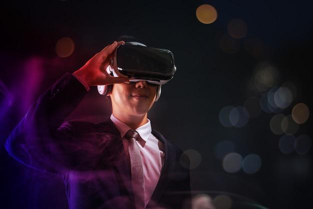 Technologie en digitaal bedrijfsinnovatieconcept, zakenman die glazen virtuele werkelijkheidsbeschermende brillen dragen bij nacht met zacht onduidelijk beeld bokeh