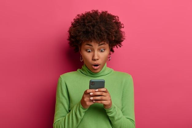 Technologie en emoties concept. verbaasde vrouw met donkere huid gebruikt moderne mobiele telefoon, staart naar het display, verrast door goede gadget, chats online