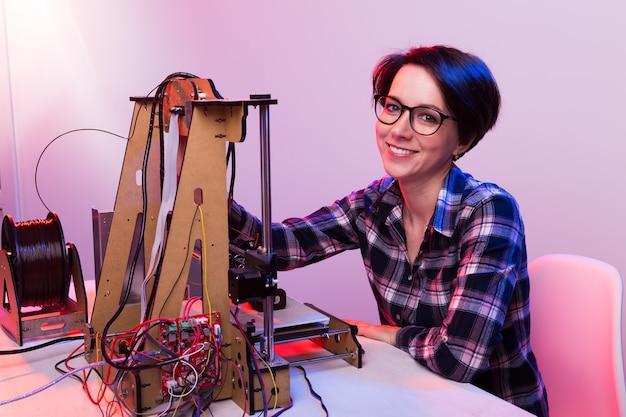 Technologie en engineering concept - vrouwelijke ingenieur die 's nachts in het lab werkt, hij past een 3d-printercomponenten aan