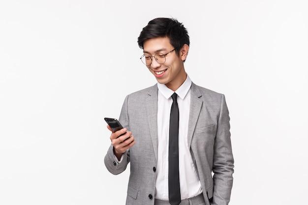 Technologie en financiënconcept. taille-up portret van tevreden knappe mannelijke ondernemer, bedrijfseigenaar in grijs pak, glimlachend tevreden als goede tekstbericht ontvangen op smartphone, op een witte muur