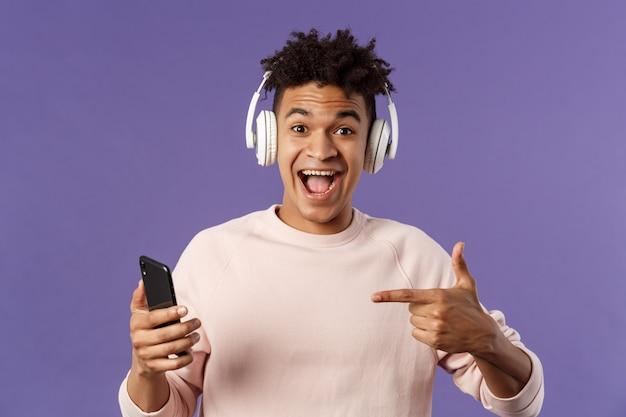 Technologie en levensstijlconcept. portret van een gelukkige, vrolijke jongeman die geweldige podcast of online muziekplatform aanbeveelt, abonnementen koopt, op elk moment liedjes luistert, koptelefoon draagt, naar telefoon wijst