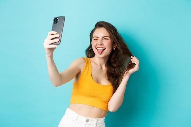 Technologie en lifestyle concept. gelukkige jonge vrouw die gekke gezichten trekt terwijl ze selfie neemt op smartphone-app met filters, staande tegen een blauwe achtergrond.