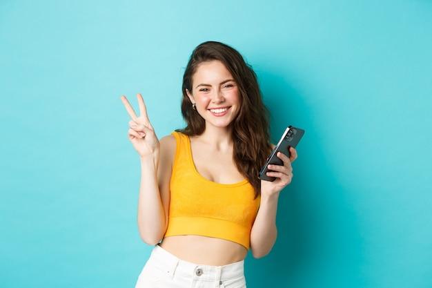 Technologie en lifestyle concept. mooi vrolijk meisje dat positieve vibes verzendt, glimlacht en vredesteken toont, mobiel gebruikt, staande tegen een blauwe achtergrond.