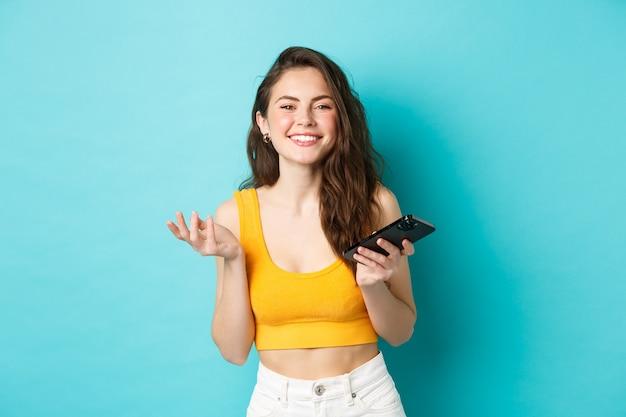 Technologie en lifestyle concept. mooie blanke vrouw chatten op telefoon, smartphone houden en lachend op camera, blauwe achtergrond.