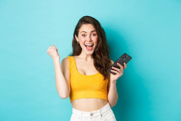 Technologie en lifestyle concept. opgewonden vrouw die online wint, smartphone vasthoudt en ja-vuistpompgebaar maakt, viert, doel bereikt in app, blauwe achtergrond.