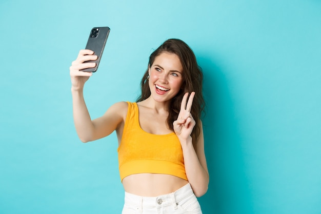 Technologie en lifestyle concept. stijlvolle jonge vrouw die selfie in haar zomerkleren neemt, v-teken toont op smartphonecamera, staande over blauwe achtergrond