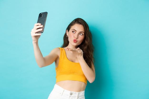 Technologie en lifestyle concept. stijlvolle mooie vrouw poseren voor selfie, luchtkus naar camera sturen, app voor fotofilters gebruiken op mobiele telefoon, staande tegen blauwe achtergrond