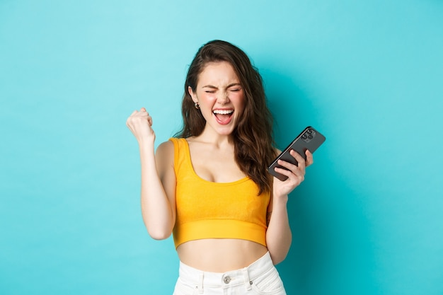 Technologie en lifestyle concept. tevreden vrouw behaalt succes, wint op mobiele telefoon, maakt vuistpomp en schreeuw ja met vreugdevolle uitdrukking, staande over blauwe achtergrond.