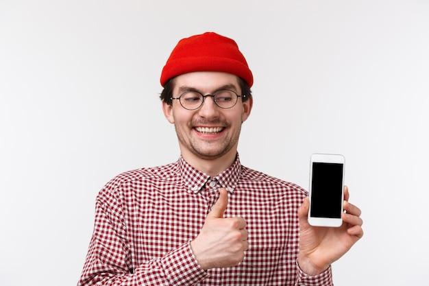Technologie en mensen concept. close-up portret geeky schattige bebaarde man met tevreden gelukkige glimlach, kijkend naar het scherm van de mobiele telefoon, geef thumb-up in goedkeuring, stel een coole app voor,