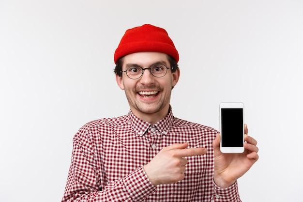 Technologie en mensen concept. close-up portret gelukkig lachend jonge bebaarde hipster man met mobiele telefoon, wijzend smartphone-display aanbevelen download app, opscheppen met geweldige match