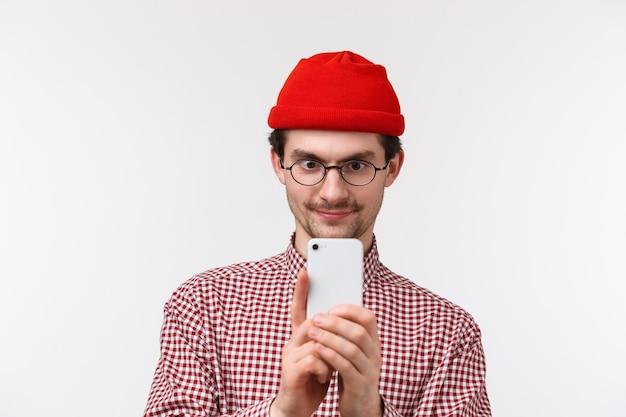 Technologie en mensen concept. close-up portret opgewonden knappe bebaarde man in rode muts en bril video opnemen op smartphone, foto van iets cools, mobiele telefoon vast te houden