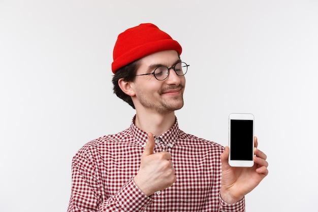 Technologie en mensen concept. close-upportret tevreden gelukkige jonge hipstermens in rode muts en glazen, tevreden kijkend op vertoning van de mobiele telefoon, maak thumb-up smartphone-gadget goedkeuren