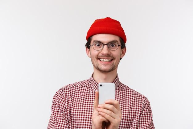 Technologie en mensen concept. de opgewekte knappe jonge hipsterkerel woont geweldig concert bij en neemt het op mobiele telefoon op, houdend geamuseerd glimlachen van de telefoon, witte muur