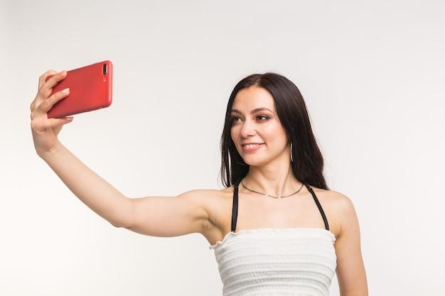 Technologie en mensen concept - jonge vrouw die een selfiefoto maakt en op witte muur glimlacht.