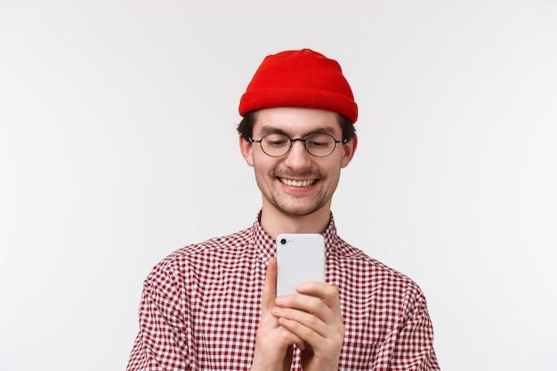 Technologie en mensen concept. mooie glimlachende jongeman video opnemen, foto nemen van zijn vriendin op het podium, mobiele telefoon fotograferen of online streamen,