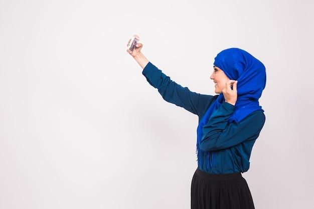 Technologie en mensen concept - moslimvrouw in hijab nemen foto op smartphone op witte achtergrond.