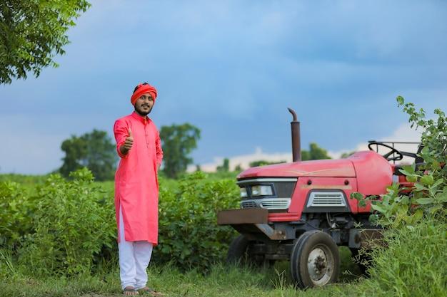 Technologie en mensen concept, portret van jonge indiase boer met tractor
