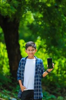 Technologie en mensenconcept - glimlachende tiener in blauw overhemd die smartphone met het lege scherm tonen