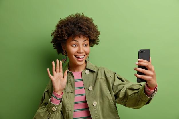 Technologie en online levensstijlconcept. de glimlachende vrouw zegt hallo geniet van videogesprekken maakt gebruik van snelle internetverbinding, gekleed in modieus jasje dat op groene muur wordt geïsoleerd
