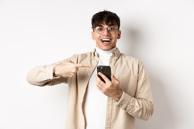 Technologie en online winkelconcept. gelukkig hipster kerel wijzende vinger op het smartphonescherm en glimlachen, app-promo uitchecken, staande op de witte muur.