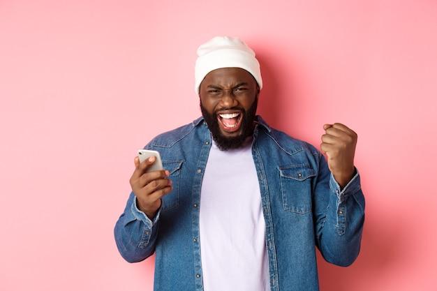 Technologie en online winkelconcept. gelukkige zwarte man verheugt zich, wint in app, houdt smartphone vast en schreeuwt ja, staande over roze achtergrond