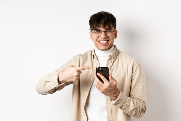 Technologie en online winkelconcept. portret van natuurlijke man in glazen lachen en vinger wijzen naar smartphone, promo-aanbieding op scherm tonen, staande witte muur.