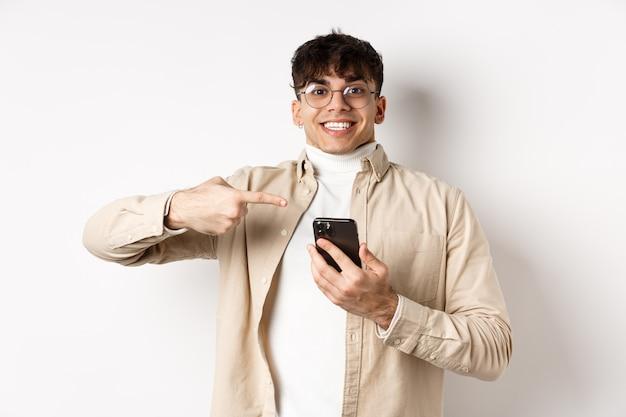 Technologie en online winkelconcept. vrolijke jonge man in glazen tonen op mobiele telefoon, wijzend op het smartphonescherm en glimlachend opgewonden, witte muur.