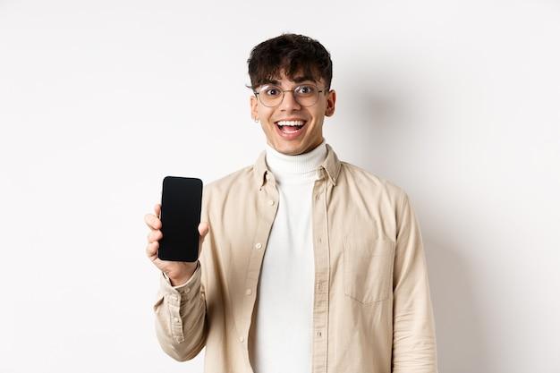 Technologie en online winkelconcept. vrolijke knappe kerel in glazen die het lege smartphonescherm tonen en glimlachen, toepassing tonen, die zich op witte muur bevinden.