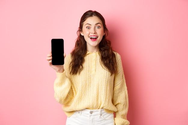 Technologie en online winkelen. aantrekkelijke studente kijkt opgewonden, toont leeg smartphonescherm en glimlacht, staat tegen roze muur.