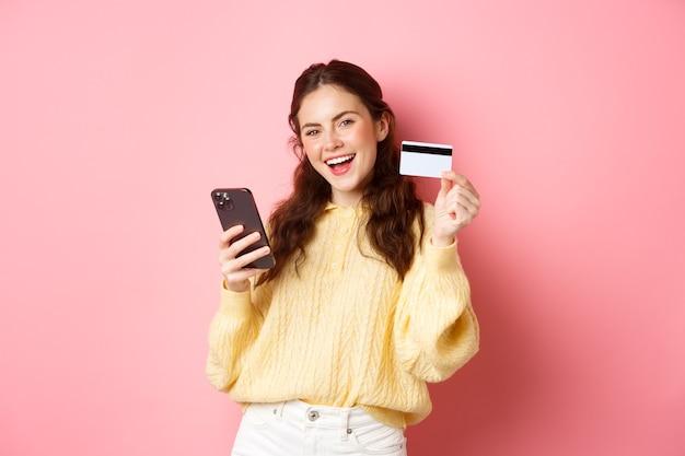 Technologie en online winkelen. blije en tevreden vrouwelijke klant, die plastic creditcard toont en de mobiele telefoon-app gebruikt om online te betalen, staande tegen de roze muur.