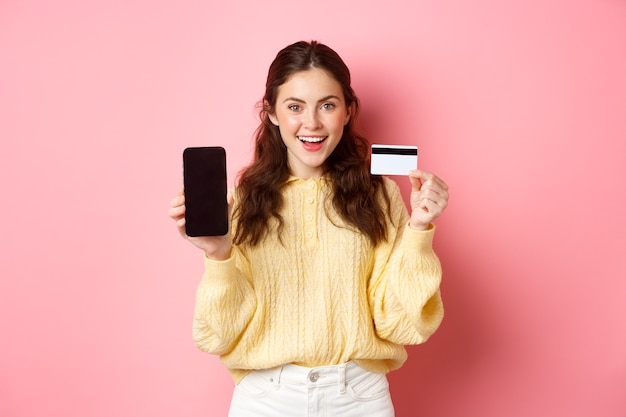 Technologie en online winkelen. jong aantrekkelijk vrouwelijk model dat het lege smartphonescherm met plastic creditcard toont, toont bankrekening of toepassing, die zich over roze muur bevindt.