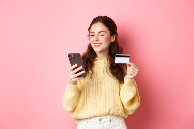 Technologie en online winkelen. jonge mooie dame die online met creditcard betaalt, smartphone bekijkt en glimlacht, die zich over roze muur bevindt.