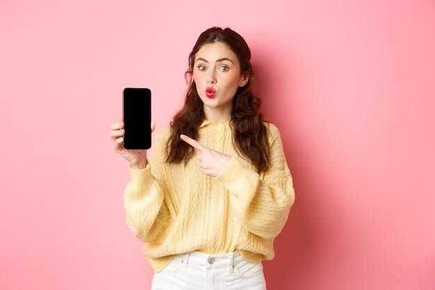 Technologie en online winkelen. opgewonden meisje kijkt nieuwsgierig, wijst met de vinger naar het lege gsm-scherm, toont app op smartphone, staande tegen roze muur.