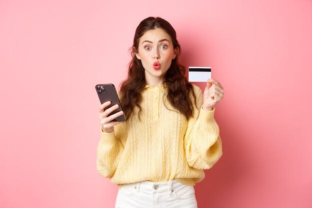 Technologie en online winkelen. opgewonden meisje shopper plastic creditcard tonen en mobiele telefoon vasthouden, betalen met smartphone, online bestellen, staande tegen roze muur.