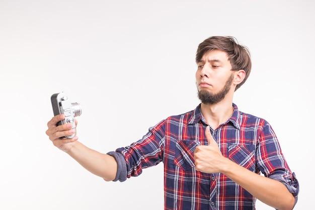 Technologie, fotografie en mensenconcept - knappe man in geruit hemd die selfies neemt op vintage camera